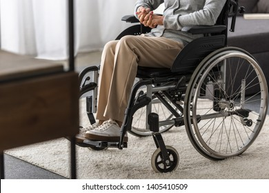 partial view of disabled senior woman in wheelchair at home