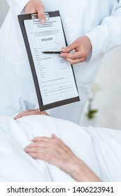 partial view of doctor holding clipboard and pen and ill patient in clinic