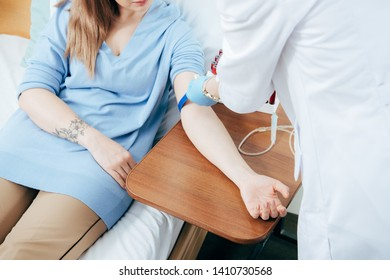 partial view of doctor using tourniquet for blood test in hospital