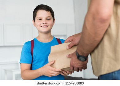 partial view of father giving paper package with food to smiling son with backpack at home