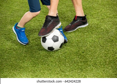 partial view of father and son playing soccer on grass