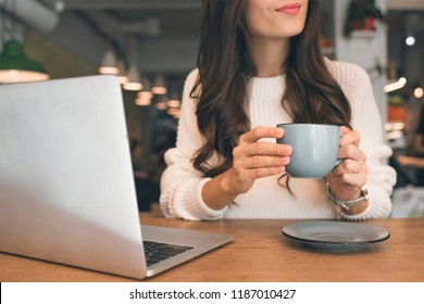 partial view of female freelancer sitting with laptop and coffee cup at table in cafe