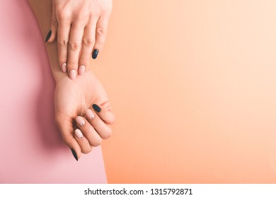 partial view of female hands with pink and black nails on bicolor background, color of 2019 concept