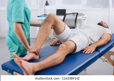 partial view of female massage therapist doing massage to patient on massage table in clinic