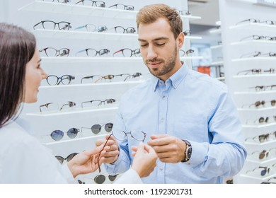 partial view of female oculist giving eyeglasses to young man in optica