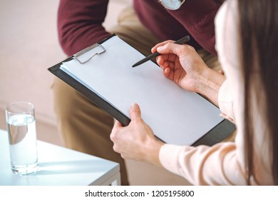 partial view of female psychologist pointing at blank clipboard during therapy appointment with male patient