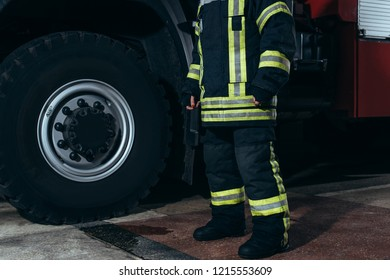 partial view of firefighter in protective fireproof uniform standing at fire station