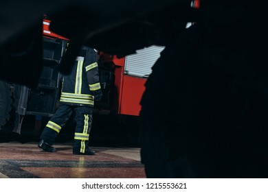 partial view of firefighter in protective fireproof uniform walking at fire station