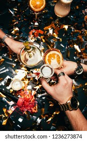partial view of friends with luxury watches clinking by glasses with alcohol over table covered by golden confetti