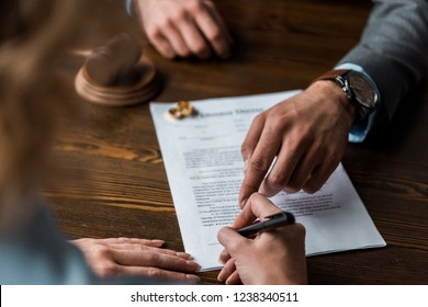 partial view of judge pointing at papers and client signing divorce decree