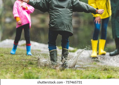 partial view of kid in raincoat and rubber boots jumping in muddy puddle in autumn forest
