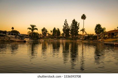 Partial view of Lake San Marcos in north county San Diego, California, USA during the sunrise time early in the morning. Palm trees and buildings reflected over the lake. Reflection is in focus only.