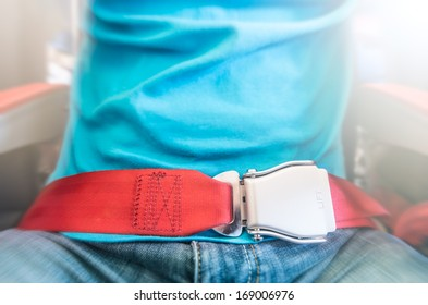 Partial view of man in blue t-shirt and jeans wearing red seat belt. Safety measures on board. Precautions on plane during flight. Comfortable and safe travelling by air.