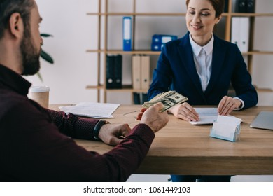partial view of man giving bribe to smiling businesswoman at workplace in office