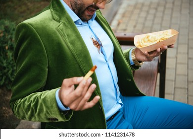 partial view of man in green velvet jacket with ketchup on shirt and french fries in hands sitting on bench on street