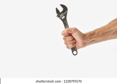 Partial view of man holding monkey wrench isolated on white