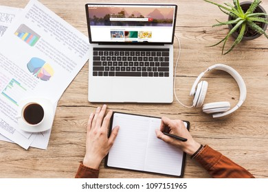 partial view of man making notes in notebook at workplace with laptop with shutterstock website, papers, cup of coffee and headphones
