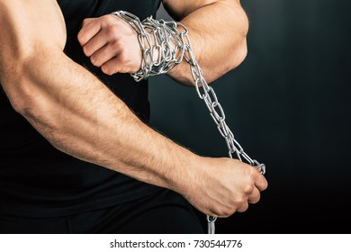 partial view of man with metal chain on hands isolated on black