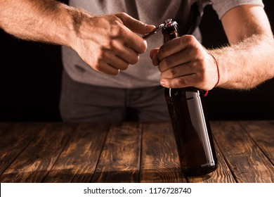 partial view of man opening beer bottle by opener at wooden table