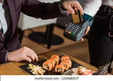 Partial view of man paying by credit card for dinner in restaurant