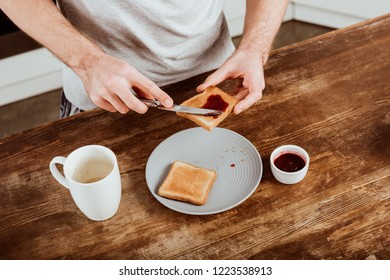 partial view of man spreading toast by jam at table with coffee cup in kitchen at home
