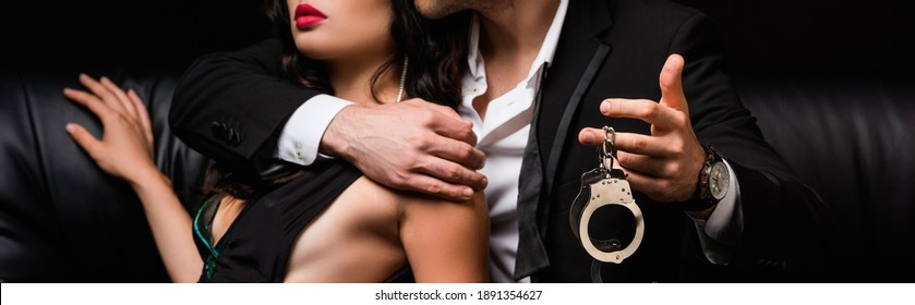 partial view of man in suit holding handcuffs near sexy woman, banner