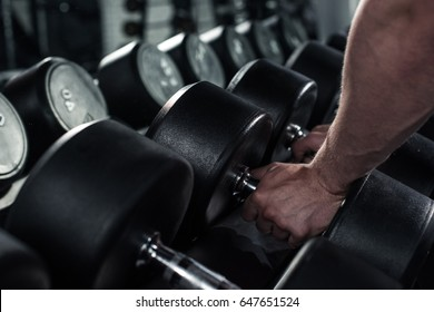 partial view of man taking dumbbells for exercising at gym