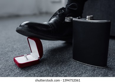 partial view of man trampling gift box with ring near flask on floor