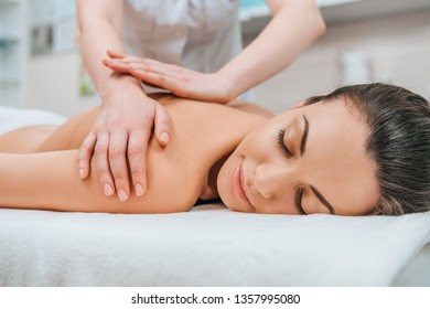 Partial view of masseur doing back massage to girl on massage table