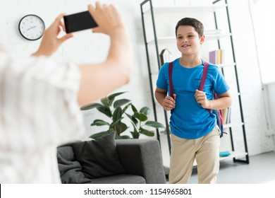 partial view of mother taking picture of son with backpack at home, back to school concept