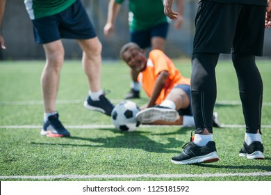 partial view of multicultural elderly friends playing football together