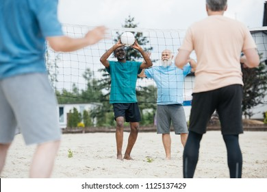 partial view of multicultural old friends playing volleyball on beach on summer day