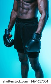 partial view of muscular african american sportsman in shorts and boxing gloves on blue background