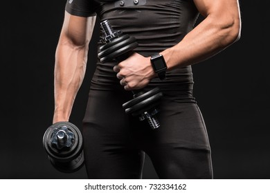 partial view of muscular man holding dumbbells isolated on black