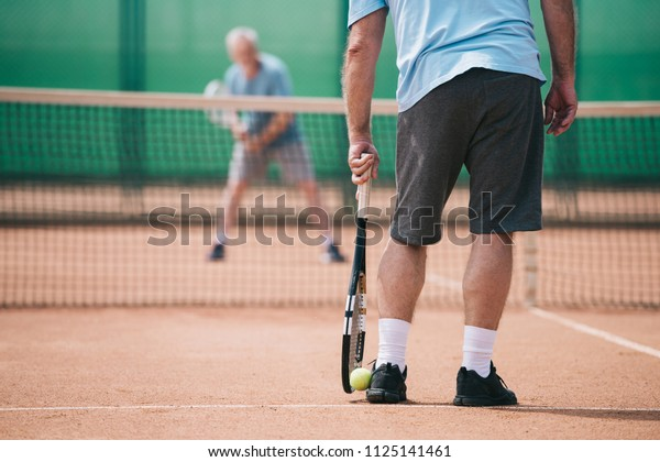 partial view of old man playing tennis with friend in court