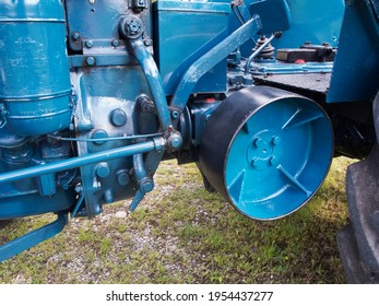 Partial view of an old and restored tractor in blue with a view of the belt drive line for a transmission belt and the steering and coupling linkage.