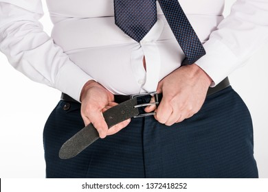 partial view of overweight man in formal wear putting on tight pants isolated on white