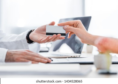 partial view of patient giving credit card to doctor in clinic