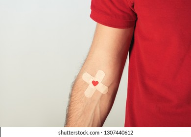 Partial view of patient in red t-shirt with plasters on grey background, blood donation concept