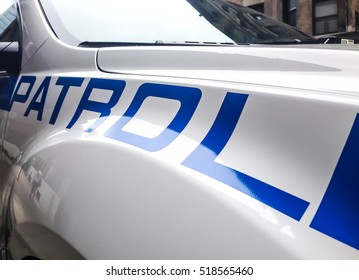 """A partial view of a patrol car zoomed in on the word """"Patrol""""."""