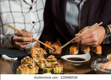 Partial view of people eating sushi rolls in restaurant