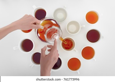 partial view of person pouring herbal tea in cups on grey