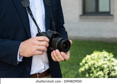 partial view of photojournalist in suit with digital photo camera