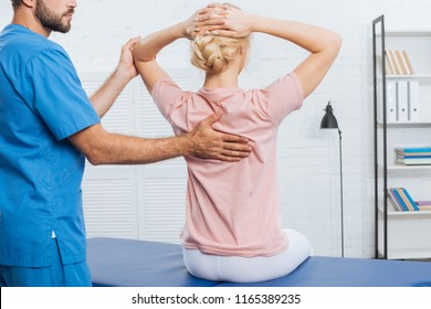 partial view of physiotherapist doing massage to woman on massage table in hospital