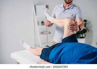 partial view of rehabilitation therapist massaging senior mans leg on massage table