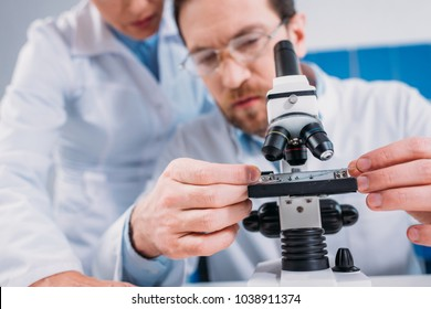 partial view of scientists in white coats working with reagent together in lab