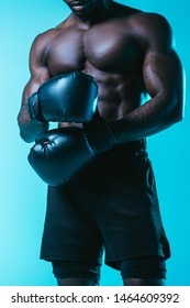 partial view of shirtless, muscular african american sportsman in boxing gloves on blue background