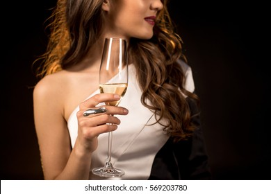 Partial view of smiling gorgeous woman holding champagne glass isolated on black