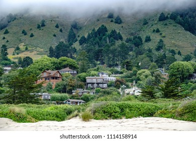 Partial view of Stinson Beach in Marin County, California, USA, between edge of sandy beach and fog over wooded foot of mountain, near the end of May