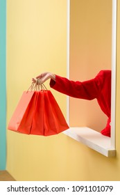 partial view of stylish woman in red clothing with red shopping bags outstretching hand out decorative window